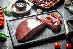 Pokrojona surowa wątróbka z pomidorami, ziele i pikantność, fotografia stock