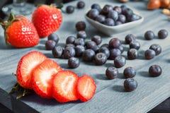 Pokrojona truskawka z czarnymi jagodami na drewnianym stole Fotografia Stock