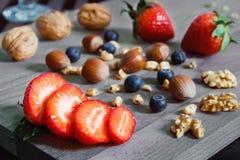 Pokrojona truskawka z dokrętkami na drewnianym stole Zdjęcie Stock