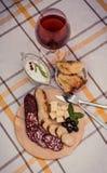 Pokrojona uwędzona kiełbasa, miękki ser, robić kiełbasa, robić chlebowy chleb na drewnianym talerzu Fotografia Stock