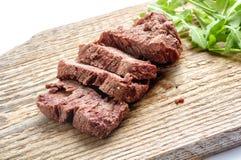Pokrojona wołowina słuzyć z świeżym greenery na starej nieociosanej drewnianej ciapanie desce Obraz Stock