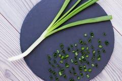 Pokrojona zielona cebula na łupkowej desce Obrazy Stock