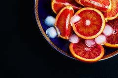 Pokrojone Sycylijskie czerwone pomarańcze na błękitnym talerzu Czarny kamienny tło, Odgórny widok zdjęcia royalty free