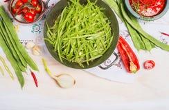 Pokrojone zielone francuskie fasole w kucharstwa naczyniu z warzywami gotuje składniki na białym drewnianym tle, odgórny widok Obraz Stock