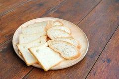 Pokrojonego białego chleba i Francuskiego chleba baguette na drewnianej desce Fotografia Stock
