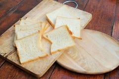 Pokrojonego białego chleba i Francuskiego chleba baguette na drewnianej desce Obrazy Stock
