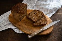 Pokrojony żyto chleb z słonecznikowymi ziarnami na drewnianej tnącej desce na ciemnym nieociosanym tle kosmos kopii obraz stock