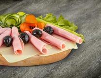 Pokrojony baleronu salami dekorował na drewnianej desce z oliwkami, pomidor Obrazy Royalty Free
