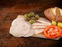 Pokrojony baleronu salami dekorował na drewnianej desce z oliwkami, pomidor Zdjęcie Stock