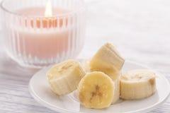 Pokrojony banan na białym talerzu i lekkim drewnianym stole Różowa płonąca świeczka niedaleka obrazy stock