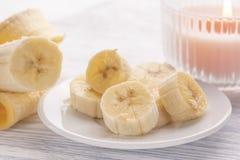 Pokrojony banan na białym talerzu i lekkim drewnianym stole Różowa płonąca świeczka niedaleka obraz stock