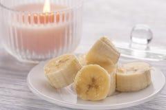 Pokrojony banan na białym talerzu i lekkim drewnianym stole Różowa płonąca świeczka niedaleka obrazy royalty free