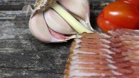Pokrojony bekon, pomidory i czosnek żarówka na starym drewnianym biurku, zbiory