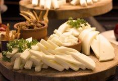 Pokrojony biały ser z zieleniami na drewnianej desce Selekcyjny foc fotografia stock