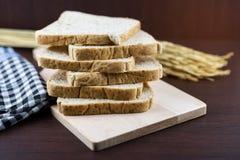 Pokrojony Całej banatki chleb na ciapania drewnie i tablecloth backgro Fotografia Stock