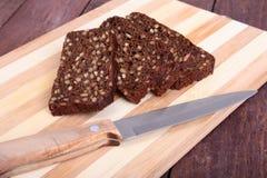 Pokrojony czarny chleb i nóż na starej drewnianej desce Fotografia Royalty Free
