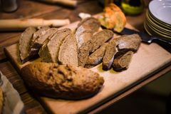 Pokrojony czarny chleb na starej drewnianej desce obraz royalty free