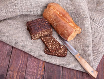 Pokrojony czarny chleb na starej drewnianej desce Zdjęcia Royalty Free