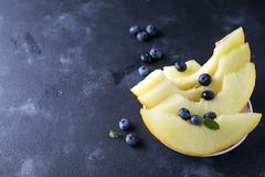 Pokrojony dojrzały melon na talerzu na ciemnym kamiennym tle zdjęcia royalty free
