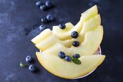 Pokrojony dojrzały melon na talerzu na ciemnym kamiennym tle obrazy stock