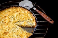 Pokrojony domowej roboty quiche z kurczakiem, cebula, pietruszka i pizza nóż na czarnym tle, serową i zieloną zdjęcie royalty free