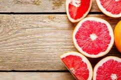 Pokrojony grapefruitowy i połówki na drewnianym tle Pożytecznie cytrus diety owoc Odbitkowa przestrzeń, odgórny widok, mieszkanie fotografia stock