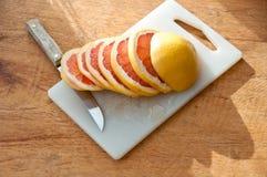 Pokrojony grapefruitowy z nożem Zdjęcia Stock