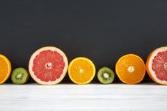 Pokrojony kiwi, pomarańcze, grapefruitowy, i mandarynka na czarny i biały drewnianym tle obraz stock