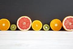Pokrojony kiwi, pomarańcze, grapefruitowy, i mandarynka na czarny i biały drewnianym tle zdjęcie stock