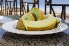 Pokrojony melon na bielu talerzu, boczny widok fotografia royalty free