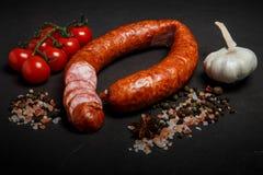 pokrojony okrąg uwędzona kiełbasa z czosnkiem i pomidorami czereśniowymi obraz stock