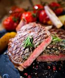 Pokrojony piec na grillu mięsny grilla stek Striploin z noża i rozwidlenia cyzelowaniem ustawiającym na czerń kamieniu krytykuje fotografia stock