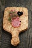 Pokrojony salami z pieprzem na oliwki desce Obrazy Royalty Free