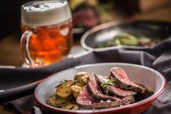 Pokrojony wołowiny tenderloin piec stek grul rozmaryny i szkicu piwo zdjęcia stock