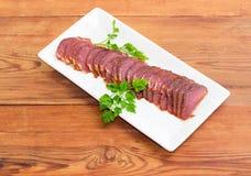 Pokrojony wysuszony wieprzowiny tenderloin z pietruszką kapuje na białym naczyniu Zdjęcia Royalty Free