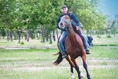 Pokrov, Ucrania - 27 de mayo de 2017: Hombre joven del jinete en un caballo que galopa en la demostración en la atracción de la c Foto de archivo libre de regalías
