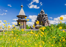 The Pokrovskaya church and the bellfry seen through the thickets of Ranunculus acris. Royalty Free Stock Photos