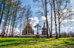The Pokrovskaya church, the bellfry and the wayside cross behind the birch trees. Stock Images