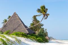 Pokrywający strzechą bungalowy na białej piaskowatej plaży otaczającej drzewko palmowe oceanem Obraz Stock