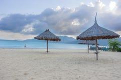 Pokrywający strzechą parasols na wybrzeżu unspoiled i wielki i relaksujący wakacje w południowo-wschodni Asia fotografia royalty free