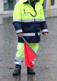 Polícia com a bandeira vermelha para sinalizar o corte de estrada Fotografia de Stock Royalty Free