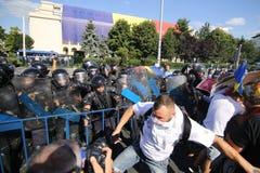A polícia de motim pulveriza o gás lacrimogêneo ao lutar com os protestadores Imagem de Stock Royalty Free