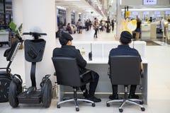 A polícia do aeroporto no dever usando Segway para patrulhar e na segurança em torno do terminal para impede o terrorista Imagens de Stock