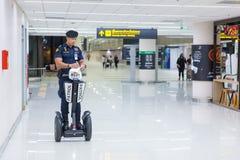Polícia do aeroporto no dever usando Segway para patrulhar e segurança Fotos de Stock Royalty Free