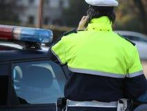 Polícia em um revestimento ao falar no telefone para segurar um em imagens de stock