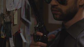Polícia fresco que recarrega sua arma no escritório, preparando-se para prender o criminoso vídeos de arquivo