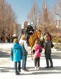 Polícia no cavalo que fala com crianças Foto de Stock Royalty Free
