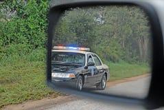 Polícia no espelho de vista traseira Fotografia de Stock