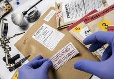 A polícia que o perito cola a etiqueta na documentação fechou-se do assassinato no cientista do laboratório fotografia de stock royalty free