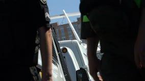 Polícias seguros que andam lentamente ao longo do parque de estacionamento que patrulha ruas da cidade vídeos de arquivo